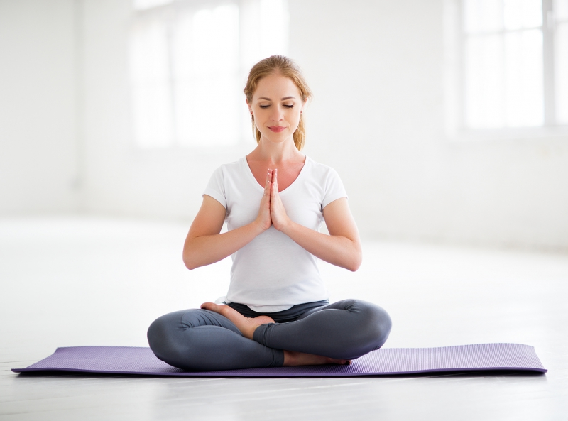 woman practicing yoga and meditating in lotus position at home
